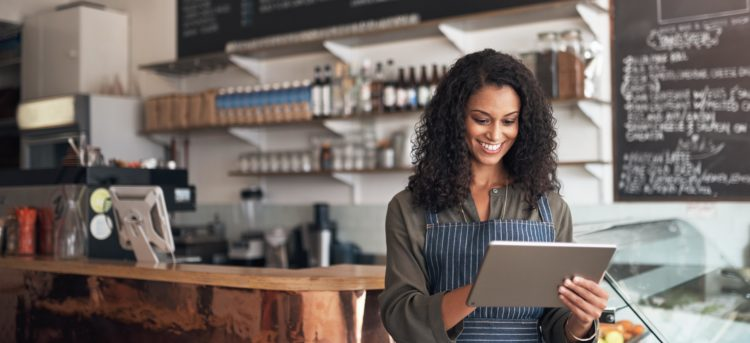 Shot of a young woman using a digital tablet while working in a cafe